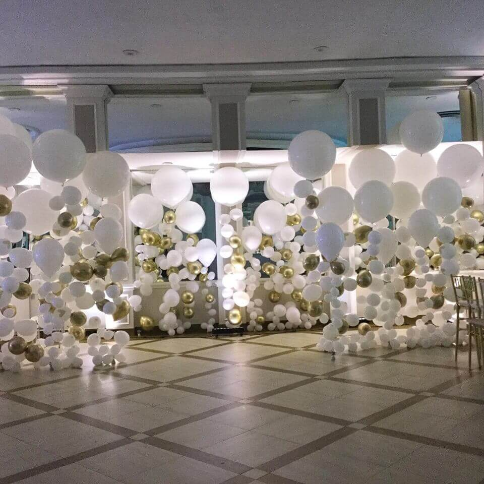 big medium and small white and gold column style balloons on strings