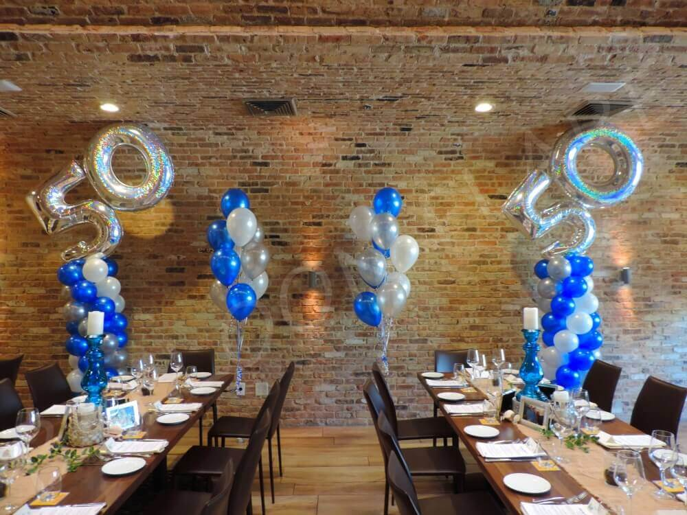 silver big 50th Mylar balloons on blue silver and white balloons column
