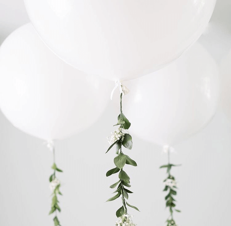 big round with green organic style garland balloon high long strings around the table